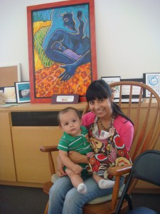 "A mother and baby with Kathy's painting ""Blue mother"" in background"